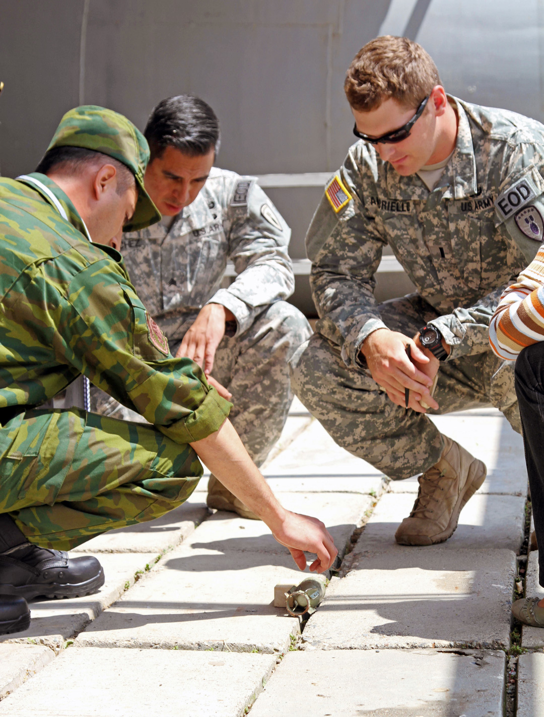 Sgt. Edgar Sanchez (center), an EOD NCO, and 1st Lt. Mitchell Amoriello, an EOD operations officer with the 75th Ordnance Disposal Company, 79th Ordnance Disposal Battalion, 71st Ordnance Group, conduct a practical exercise with a Tajikistan engineer during the International Mine Action Standard EOD level-one course in Tajikistan on June 3, 2014. (Photo by Sgt. Tracy R. Myers)