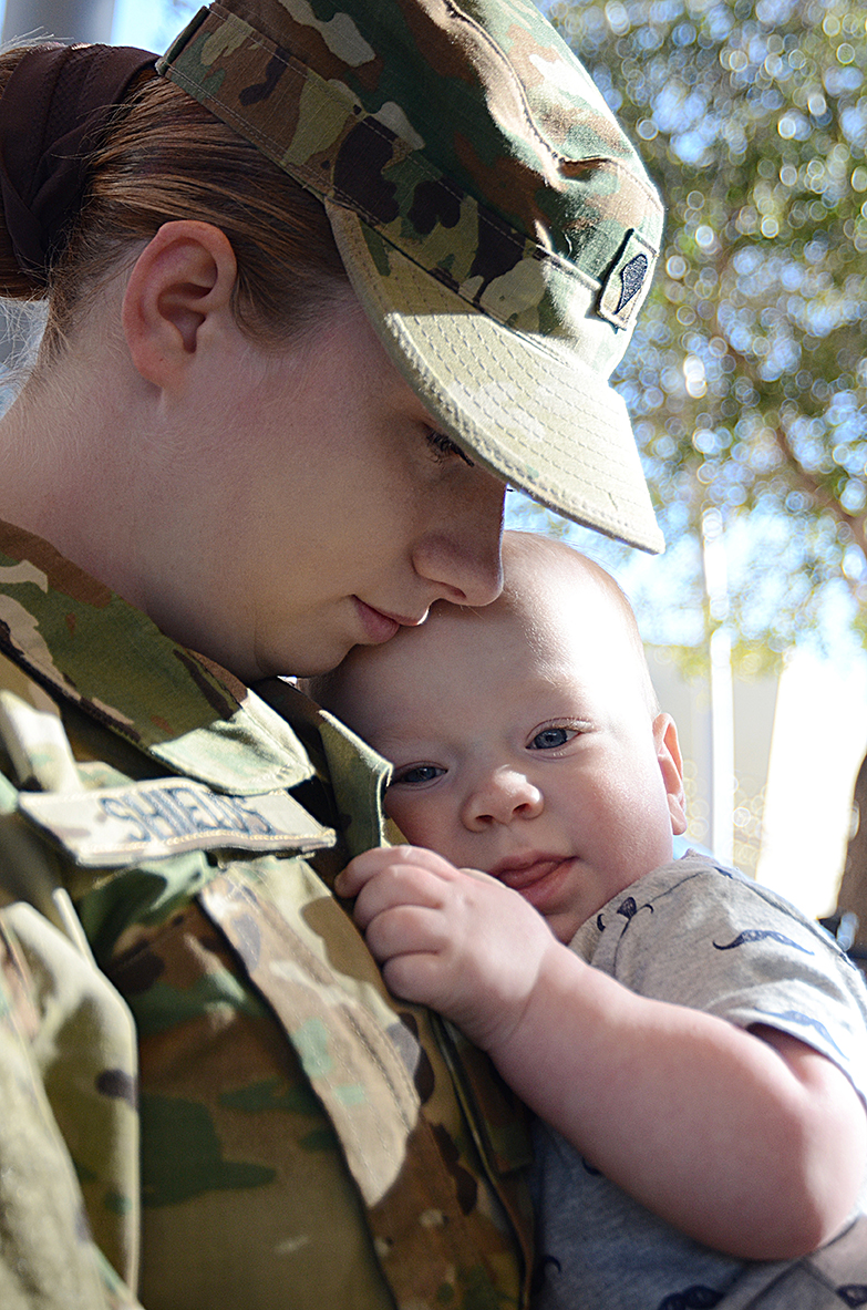 Spc. Christina Shields of Headquarters and Headquarters Company, 47th Brigade Support Battalion, 2nd Brigade, 1st Armored Division, cuddles with her 10-month-old, John Henry Jr., at Freedom Crossing, an outdoor shopping center at Fort Bliss, Texas. (Photos by Meghan Portillo / NCO Journal)