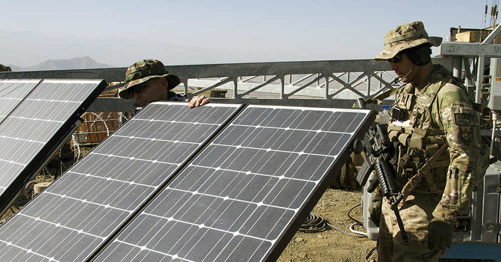 A contractor with the Rapid Equipping Force, left, shows Capt. Steven Caldwell  how to adjust solar panels to increase solar energy collection in September 2014 in  Afghanistan. (Photo by Sgt. William White / U.S. Army)
