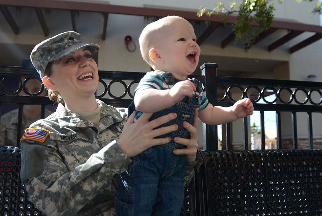 Spc. DeAmbra Meyer of Intelligence and Sustainment Company, Headquarters and Headquarters Battalion, 1st Armored Division plays with her 11-month-old son, Noah, at Freedom Crossing, an outdoor shopping center at Fort Bliss, Texas. (Photo by Meghan Portillo / NCO Journal)