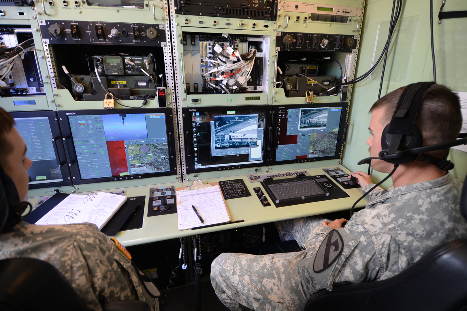 Gray Eagle UAVs are operated from within a ground control station. Spc. Zachary Zimmerman, left, works as the aircraft operator, while Staff Sgt. Mark Mushen controls the cameras and sensors as the payload operator. (Photo by Meghan Portillo/NCO Journal)