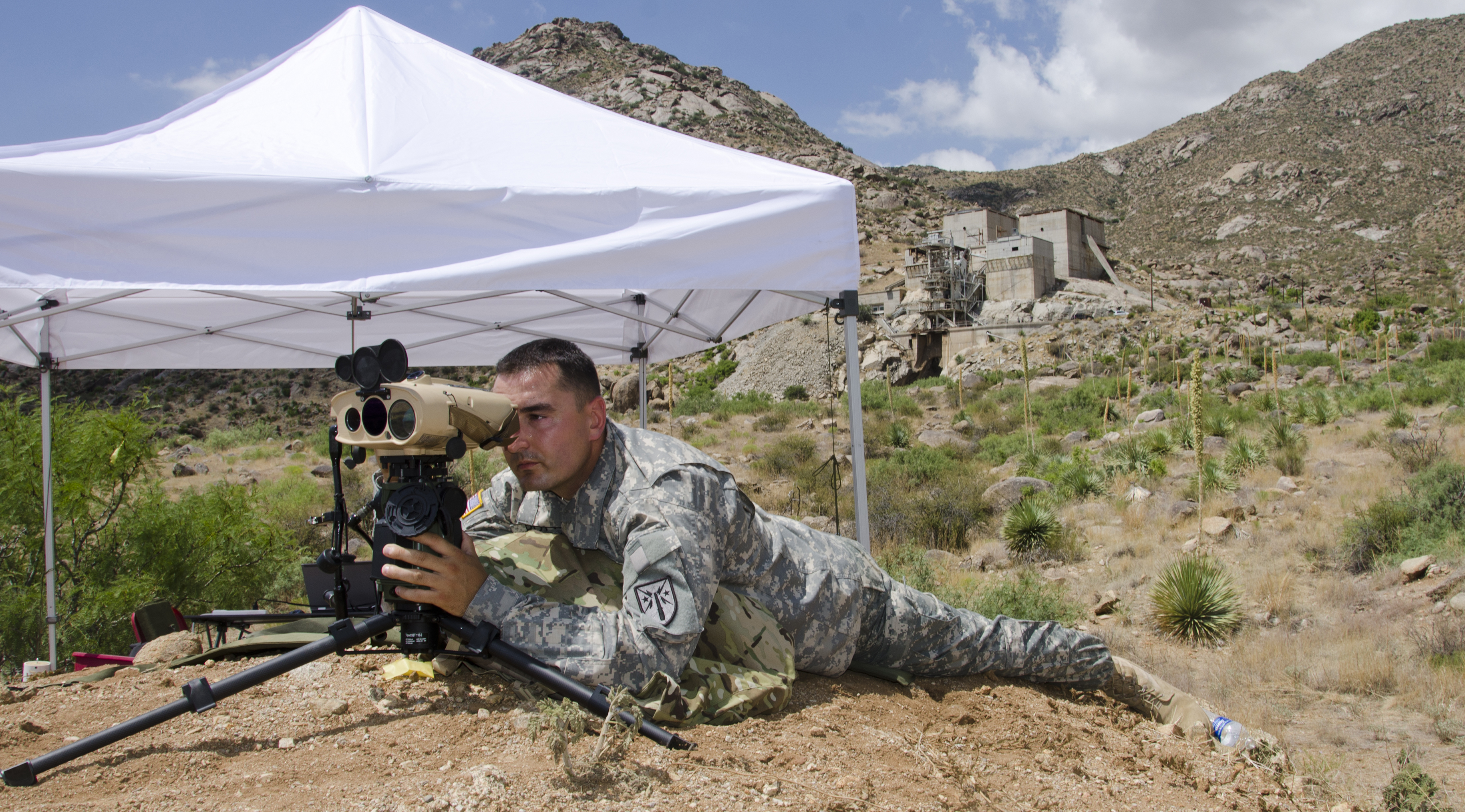 Sgt. 1st Class Justin Rotti, a combat developer for the U.S. Army Training and Doctrine Command Fire Cell, tests a developmental handheld precision targeting device for the Rapid Equipping Force in July 2014 at White Sands Missile Range, New Mexico. The device allows Soldiers to engage targets with precision munitions and provide digital connectivity to related units. (Photo by John Hamilton / White Sands Missile Range Public Affairs)
