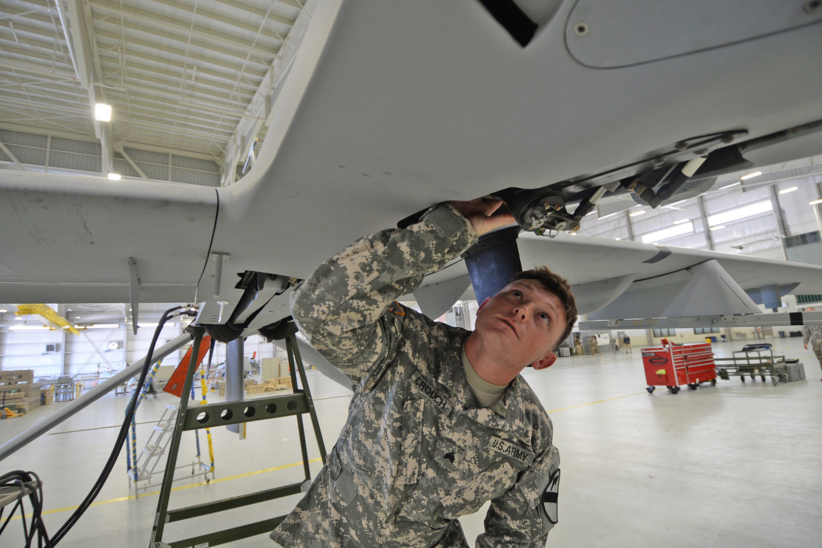 Sgt. Joseph Crouch, an unmanned aircraft systems repairer, performs preflight operational checks on a Gray Eagle UAV's landing gear. (Photo by Meghan Portillo/NCO Journal)