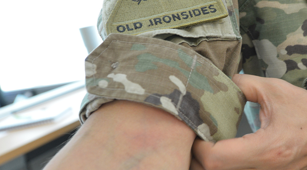 Soldier rolling up his sleeve.