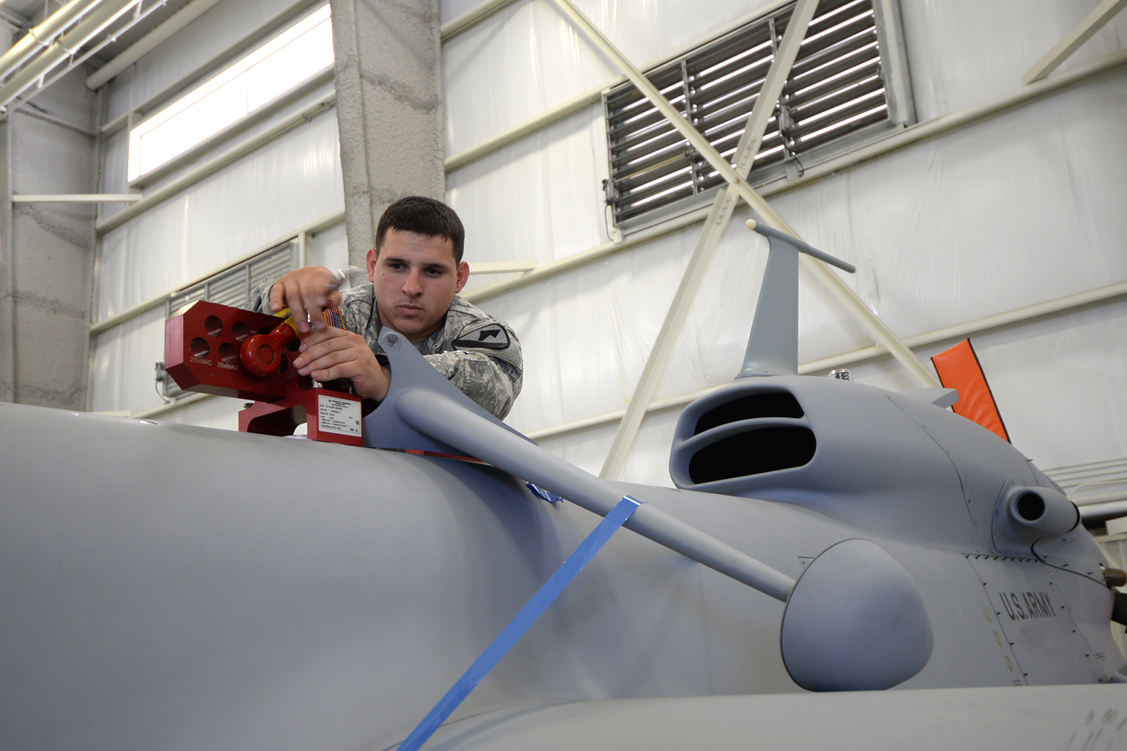 Spc. Michael Chartrand, a 15E unmanned aircraft systems repairer, performs a weight and balance check on a Gray Eagle unmanned aerial vehicle to get the drone ready to fly. (Photo by Meghan Portillo/NCO Journal)