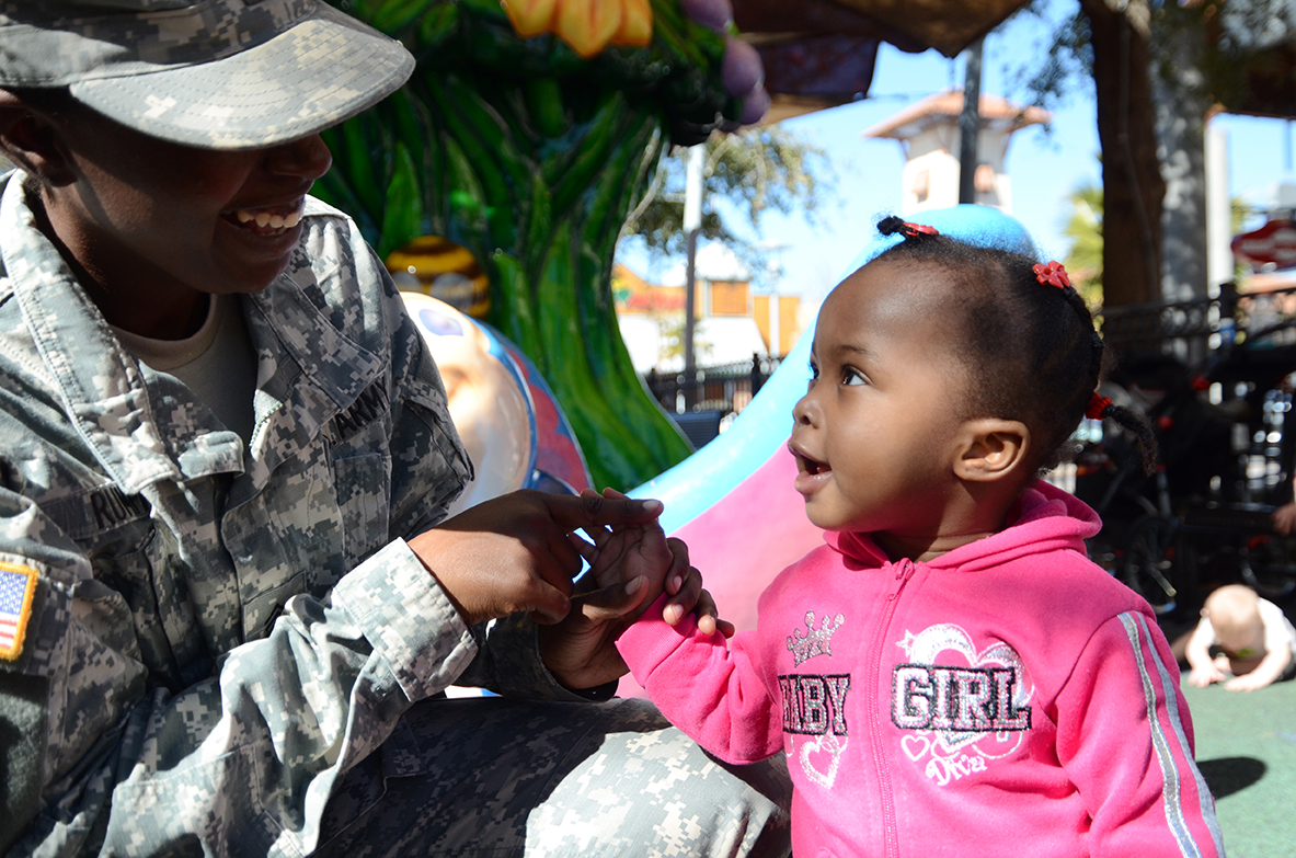 Sgt. Tiana Rumph of Headquarters and Headquarters Company, 1st Stryker Brigade, 1st Armored Division, plays with her 16-month-old, Lillian, at Freedom Crossing, an outdoor shopping center at Fort Bliss, Texas. (Photos by Meghan Portillo / NCO Journal)